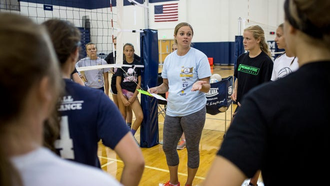 Coach Amanda Busch talks with players in a huddle during volleyball practice Thursday, August 11, 2016 at Marysville High School.