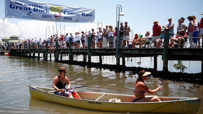 """In this file photo, Kate Lapinski, left, laughs after finishing with teammate Angel America Elza Saturday, May 14, 2016 at Crayton Cove in Naples, Fla. The 40th, and presumably final Great Dock Canoe Race, concluded with a disco theme - because it started in 1977 - titled """"The Last Dance."""" Hundreds showed up and dozens competed in themed, amateur, VIP and pro categories. The father-daughter team Bill Ervin and Adriene Ervin won the pro event with a time of 20:48 and 18:48 adjusted for a two minute handicap, since they were a mixed sex team. Best overall time was from father-son tandem Peter Jenks, 60, and Casey Jenks, 31."""