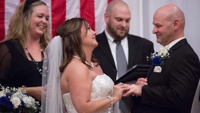 Ryan Swagler and Valerie Ashley exchange rings Friday, Aug. 12, 2016 at the Embassy Suites in downtown Des Moines Ryan Swagler is a Des Moines police officer. He's marrying Valerie Ashley. The couple moved up their nuptials a full year after assassinations of police officers in Dallas. They planned to have three vacant place settings for the three metro officers who died in the line of duty this year. They will also have 70 blue roses labeled for every law enforcement officer who has been killed in the line of duty this year. Swagler was close to Carlos and Susan, the Des Moines officers who died earlier this year. They want to the wedding to b a celebration of their love, a reminder of what police sacrifice for the job and a sort of induction into the law enforcement family for Ashley.