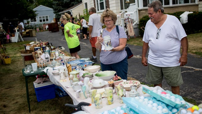 Marilyn and Joe Rini, of Port Huron, looks over items Saturday, August 13, 2016 at Mary Anne Felthouse's yard sale as part of the Yard Sale Trail on North Main Street in Marine City.