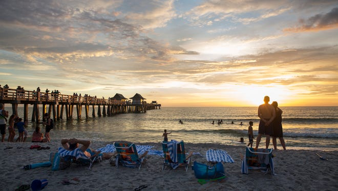 Jacqui and Mark Hallum, right, of the United Kingdom, take photos of the sunset while on vacation at the Naples Pier on August 11, 2016.