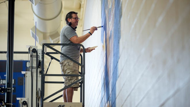 David Stoneberg, of Port Huron, puts finishing touches on a large Viking mural Thursday, August 18, 2016 at the Marysville Middle School Gymnasium.