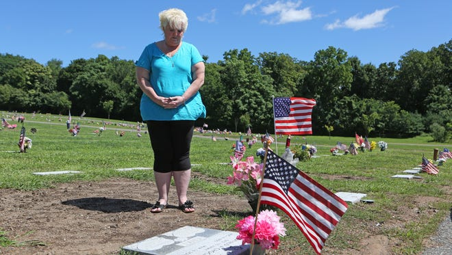 Cheryl Croci at her father's gravesite Monday at Frederick Loescher Veterans Cemetery in New Hempstead. Croci wants more security at the cemetery after flowers and other items were stolen from his grave.
