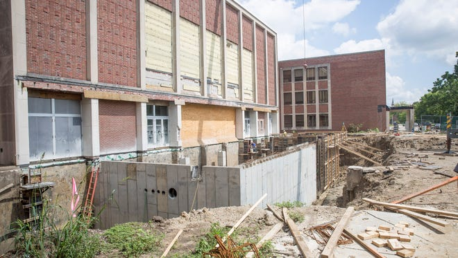 Construction crews work on the exterior of Emens Auditorium Monday afternoon. The theatre will see an expanded lobby, new front facade and additions to the second floor as well.