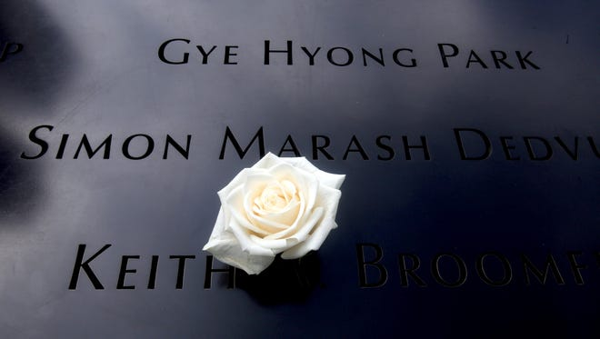 File - A flower rests on one of the names engraved at the reflecting pools at the 9/11 Memorial in lower Manhattan.