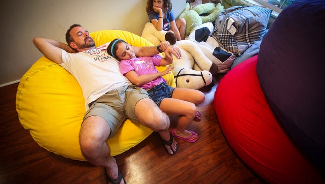 """Todd Suffering of Punta Gorda hangs with his twin daughters Olivia and Sophia, 8, before the evening got started. Their mother, Jessie, passed away last year and they have been coming to Valerie's House for the past 4 or 5 months now. """"It is the only thing their are excited about"""", Todd said. Valerie's House, a new non-profit organization that offers counseling to such survivors in a family friendly setting. The idea is to allow families going through a meet in group settings to talk about dealing with day-to-day grief."""