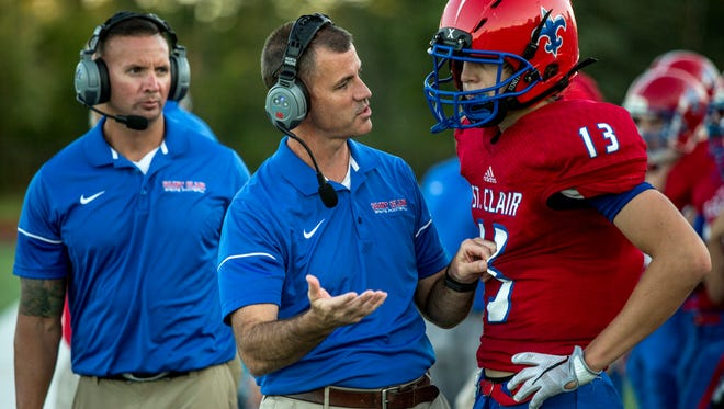 St. Clair coach Bill Nesbitt talks with Ben Davidson on the sidelines during a football game