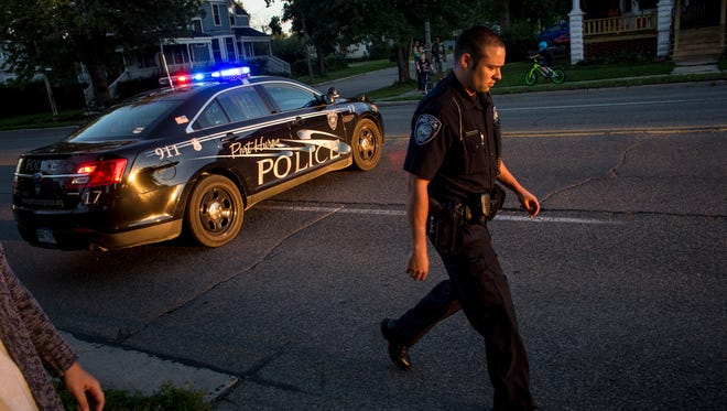 Port Huron Police Officer Derek Paret walks from his patrol car while responding to the scene of an accident Wednesday, September 14, 2016 on Lapeer Avenue in Port Huron.