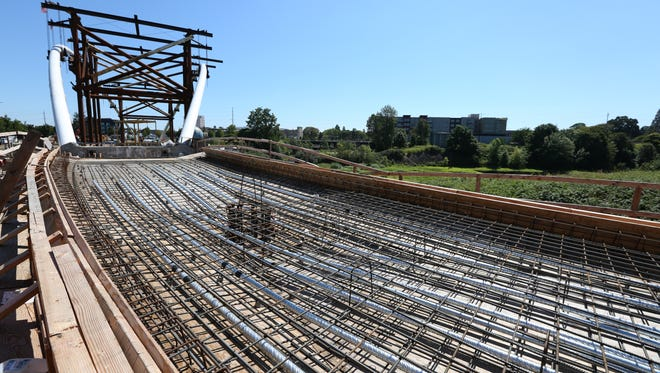 Work continues on the Peter Courtney Minto Island Bridge, a pedestrian bridge that will connect Riverfront Park with Minto-Brown Island Park, on Monday, July 25, 2016.