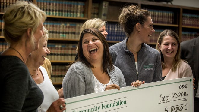 "Mara McCalmon, center, founder of the non-profit ""P.S. You're My Hero,"" smiles and laughs along with others as she is presented with a $10,000 check from the Community Foundation of St. Clair County Friday, September 23, 2016 in the victims rights office at the St. Clair County Courthouse. McCalmon has spent years volunteering at the office, working with and advocating for victims, after she survived an attack that also killed her husband 2010. The money will be spent on building a larger private space for victims and their family members within the victims rights office."