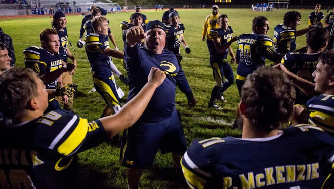 Algonac coach Jeff Smith and players celebrate beating Croswell-Lexington in a football game Friday, September 23, 2016 at Algonac High School.