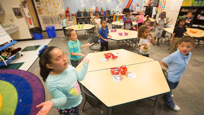 Daisy Longori,6, left, signs out the seven habits of the Leader in Me program during class on Wednesday at G. Weaver Hipps Elementary School in Lehigh Acres.