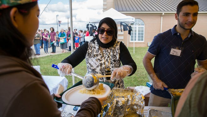 Sabeen Moin dishes out rice to hungry customers during the International Food Festival held at the Islamic Society of Evansville on Sunday morning.