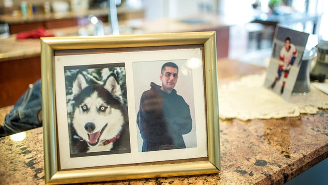 A picture of Bradley Moore and his dog, Lincoln, sits in the family room of his parents' Clyde Township home.