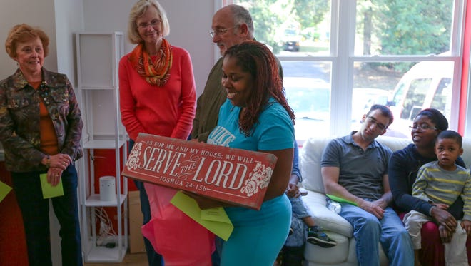 Rochelle Plummer, owner of the 38th Habitat for Humanity house in Franklin County, opens a housewarming gift in the living room of her new home.