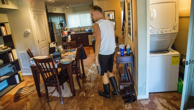 Jeremy Spearman checks on flood damage to his Parkside Five Points Townhomes apartment in Raleigh, N.C., after Hurricane Matthew caused downed trees and flooding Sunday, Oct. 9, 2016.