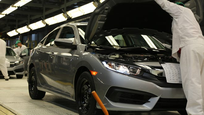 A Honda Civic is checked by a worker as it comes down the assembly line at Honda Manufacturing of Indiana's Greensburg  facility.