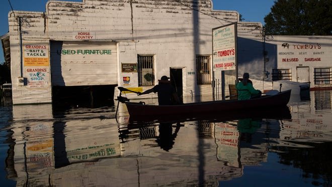 Ryan Christian and Delores Miller canoe down West 5th Street after checking on Miller's elderly mother's home in downtown Lumberton after Hurricane Matthew caused downed trees, power outages and massive flooding along the Lumber River, Tuesday, Oct. 11, 2016 in Lumberton, NC.
