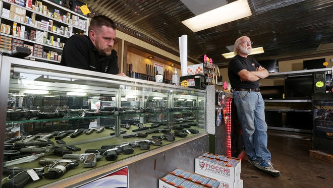Gun store owner Brandon Haling of Armed Sources Gun & Pawn LLC, left, and customer Chris Cantrell,  talk about the current environment for selling guns.