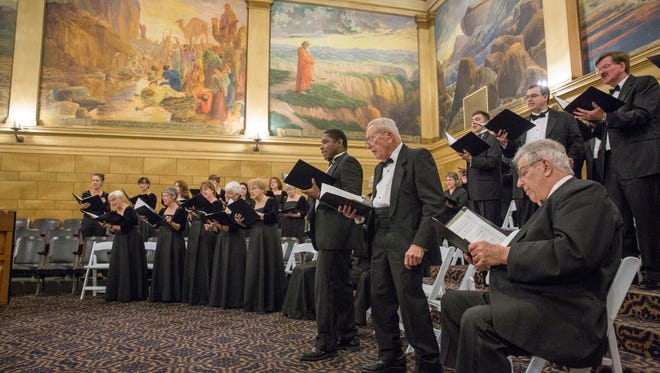 Masterworks Chorale members sing surrounded by large murals in the Legacy Room at Cornerstone Center for the Arts.