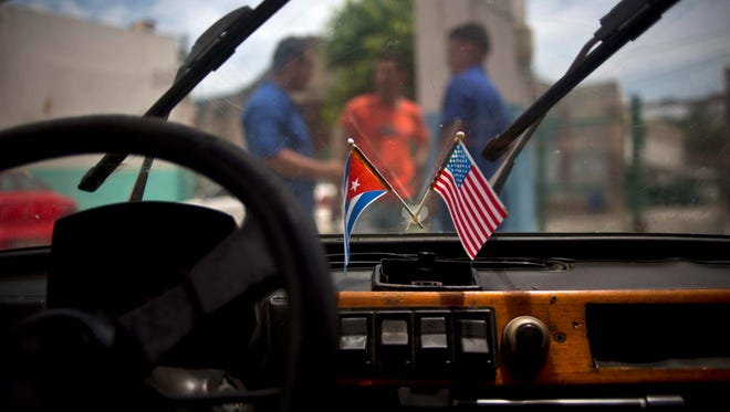 In this Aug. 10, 2016 file photo a Cuban and a U.S. flag hang on the windshield of a car in a garage in Havana, Cuba. Diplomats say the U.S. is expected to abstain, for the first time, from a U.N. resolution criticizing America's economic embargo against Cuba. Such a step would effectively pit the Obama administration, with the UN, against the Republican-led Congress, which supports the 55-year-old embargo despite the United States' resumption of full diplomatic relations with Cuba.