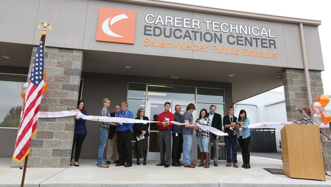 Students use sawzalls to cut the ribbon during a dedication for the Career Technical Education Center Friday, Oct. 9, 2015, in Salem.
