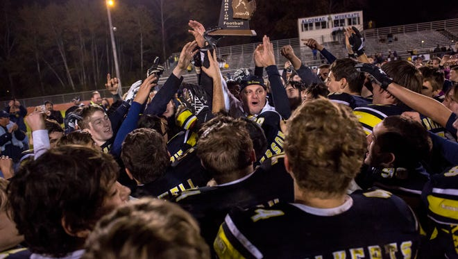 Coach Scott Barnhart raises the trophy with his team after beating Almont to win the district title Friday, Nov. 4, 2016 at Algonac High School.