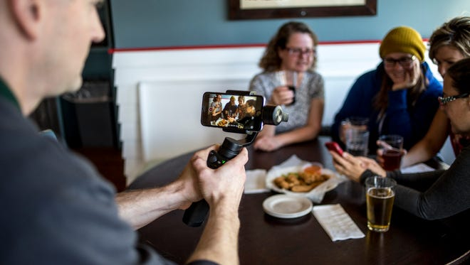 """Chris Gearhart, from Eighth Day Media, records posed participants as part of a """"Mannequin Challenge"""" video Thursday, Nov, 10, 2016 at ThumbCoast Brewing Company in Port Huron. The video is part of a Blue Water Area Convention and Visitors Bureau effort to promote Port Huron."""