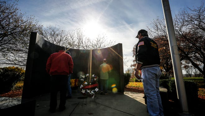 Veterans stop at the Iowa State Vietnam War memorial after a Veterans Day ceremony on the grounds of the Iowa State Capitol on Friday, Nov. 11, 2016.