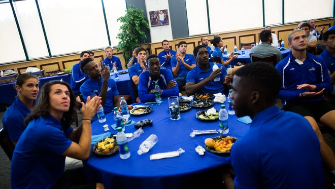 The FGCU men's soccer team claps after finding out who they will play on Thursday while watching the NCAA selection show at Alico Arena in Fort Myers. The team will be playing University of South Florida in the opening round game.