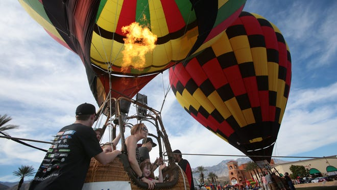 Two hot air balloons fire up their burners to take passengers up during the second Cathedral City Hot Air Balloon Festival last year. Hot air balloons return to the desert Wednesday for the annual Dinner Under the Glow event at SilverRock Resort.