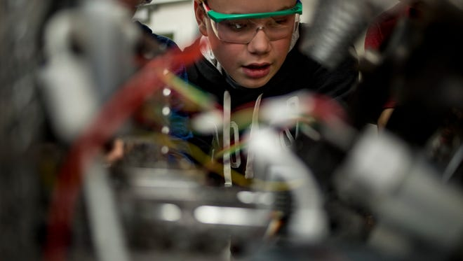 Connor Nesbitt, 14, looks closely at a component of the robot during the Vi-Bots robotics club meeting Tuesday, Nov. 15, 2016 at Marysville Middle School.