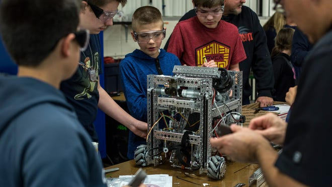 Nick Hong, 13, center, works on the robot with his teammates during the Vi-Bots robotics club meeting Tuesday, Nov. 15, 2016 at Marysville Middle School.