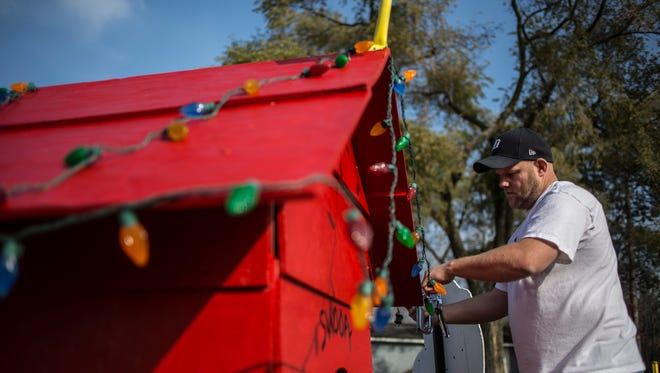 Eric Goold, of Kimball Township, puts up lights on a Charlie Brown themed display, sponsored by UAW Local 375, Thursday, Nov. 17, 2016 as part of the Christmas in the Park decoration contest at Marysville City Park. Fourteen businesses and two youth groups are participating in the contest. The displays will be completed by this weekend.
