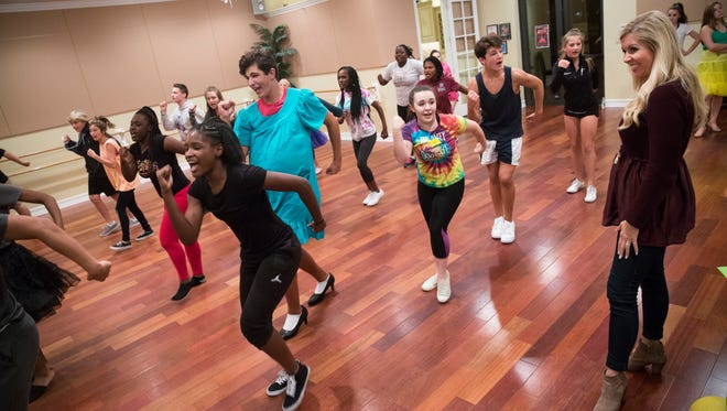 """Lori Oliver, right, the director of the show as well as the founder and president of Naples Performing Arts Center Inc., smiles as she watches the cast perform a dance number during their rehearsal for """"Hairspray"""" at the Naples Performing Arts Center in Naples on Sunday, Nov. 6, 2016. """"The musical of 'Hairspray' is about one girl who dreams. She dreams big, and she doesn't let anything get in her way,"""" Oliver said. """"I think in today's society, we still allow stereotypes or stigmas to get in our way. In this show, we have watched how color isn't an issue. They're all a family, they're all friends, they're all one."""""""