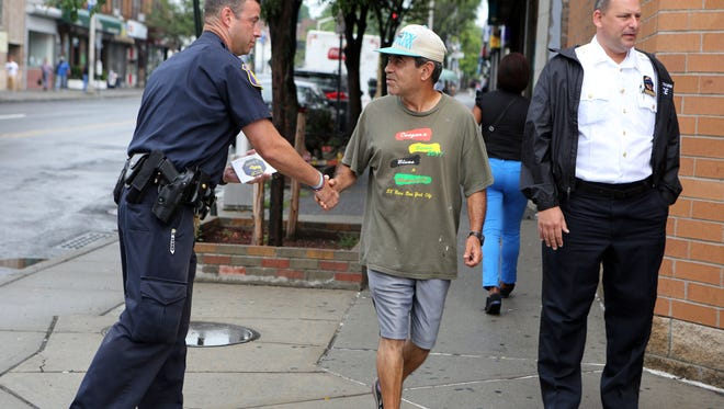 """Yonkers Police Off. David Graham shakes hands with a passerby in July as part of the YPD's """"Stop and Shake"""" program."""