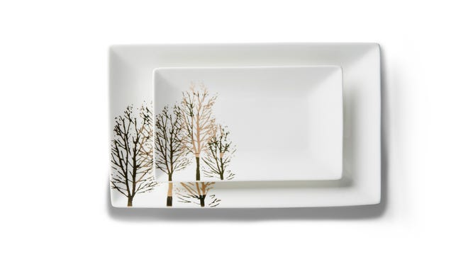 This undated photo provided by Homegoods shows a sleek, white porcelain platter featuring an elegant group of gold trees to dress it up.