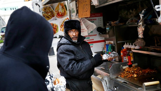 In this Nov. 21, 2016 photo, Mohammed Shaheedul Huq serves a customer from his food cart in the Brooklyn borough of New York, Monday, Nov. 21, 2016. For decades, the city's regulatory scheme has made it next to impossible to obtain a new permit to operate a food cart or truck. Unable to get a permit of his own, Huq paid $18,000 upfront to lease one from a man who pays the city just $200 every two years for the license.