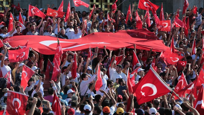 Turkish citizens wave their national flags as they protest against the military coup outside Turkey's parliament near the Turkish military headquarters in Ankara, Turkey, in July 2016.