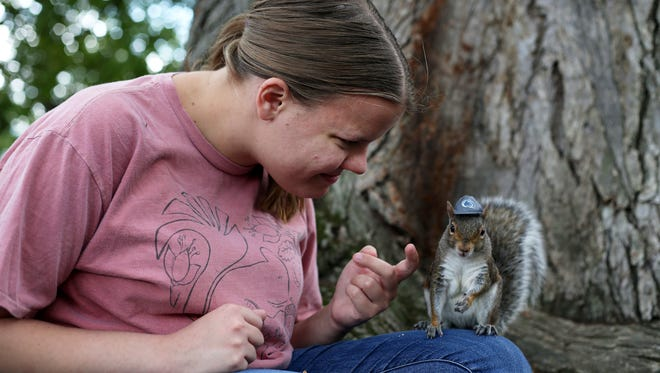 "In this Sept. 28, 2016 photo, Penn State senior Mary Krupa plays with ""Sneezy"" the squirrel on Old Main Lawn in State College, Pa. Penn State students know her as the Squirrel Whisperer, or even Squirrel Girl. Four years after she became an internet sensation, senior Krupa is still placing tiny hats on the ubiquitous rodents that live on campus, and coaxing them to hold miniature props. (Phoebe Sheehan/Centre Daily Times via AP)"