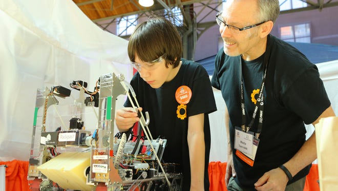 A FIRST Robotics student assembles a robot with the help of a mentor at an FRC competition.
