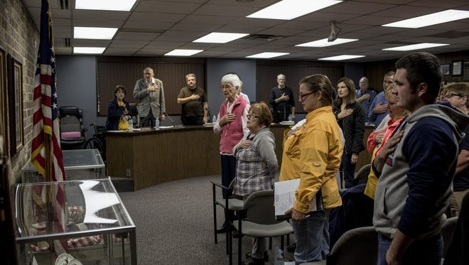 Attendees stand with their hands over their hearts as the Pledge of Allegiance is recited during a city council meeting Tuesday, Nov. 1, 2016, at Algonac City Hall.