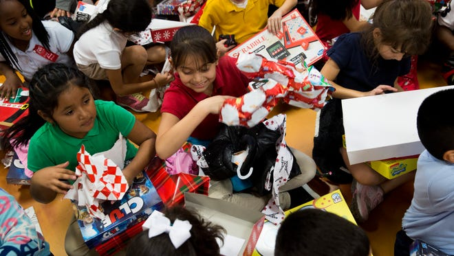 Second-graders from Manatee Elementary School unwrap presents they received from members of Elks Lodge #2010 during the 4th annual Children's Christmas Party Monday, Dec. 12, 2016, at the lodge in East Naples. Each child received a board game and an article of clothing.