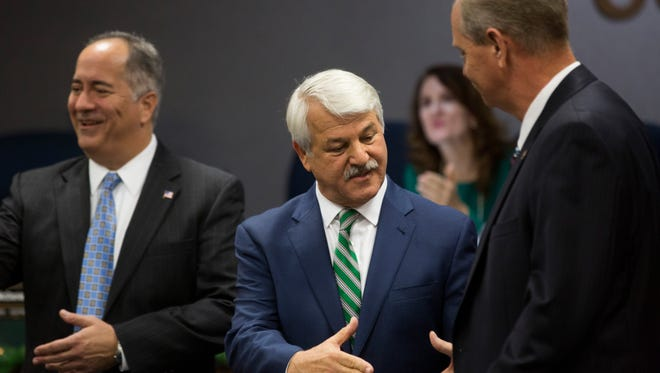 Recently elected Collier County Commissioners Andy Solis, from left, Burt Saunders, and William McDaniel congratulate each other after being sworn in to begin a Board of County Commissioners Meeting Tuesday, Dec. 13, 2016 in Naples.
