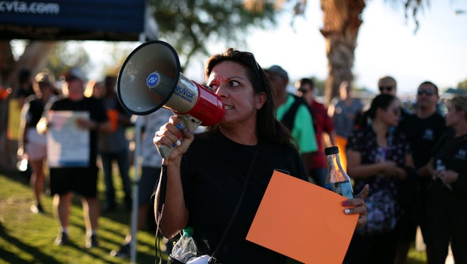 Organizer Erica Chase leads chants as about 100 educators with the Coachella Valley Teachers Association and some students gather outside the Coachella Valley Unified School District office Wednesday in support of teacher 's in labor negotiations last month.
