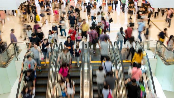 Shoppers crowd escalators at at a shopping mall.