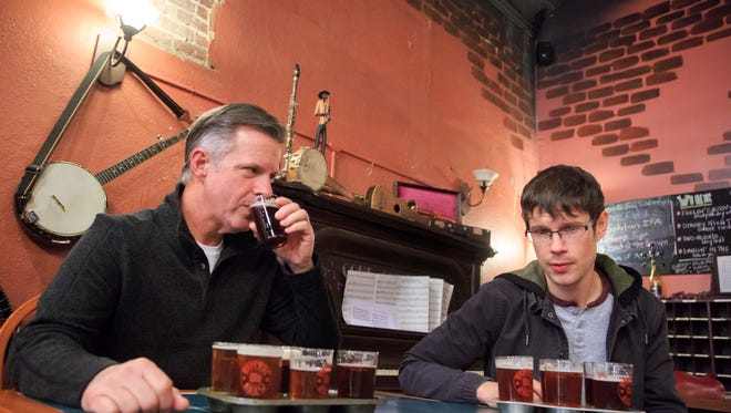 Clint Bailey and his son Marc try a flight of beer at Rustic Brew in Hampton Thursday, Dec. 15, 2016.