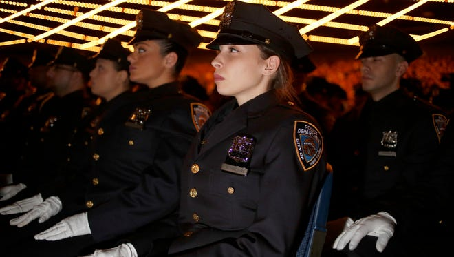 New graduates of the NYPD Police Academy participate in a graduation ceremony in New York, Wednesday, Dec. 28, 2016.