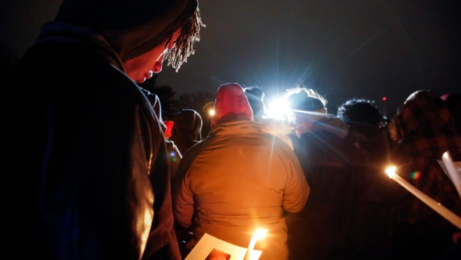 Savon Lewis holds a candle and a photo of Frederico Thompson Jr. during a vigil for Thompson at Good Park Wednesday, Jan. 4, 2017. Thompson, 18, was shot to death about 3:30 a.m. Sunday outside a southside nightclub.