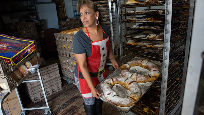 Delfina Calderon, shows a customer at Lujans Bakery a Rosca de Reyes or Kings Cake, the bakery as of 11 am had made 1,200 Kings Cakes, Friday, Jan. 6, 2016 in advance of the celebration of the Ephiphany a religious holiday marking the visit to baby Jesus by the Three Kings.